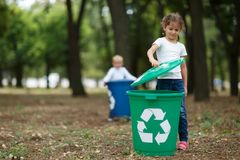 A little girl putting a bucket lid on a green recycling bin on a blurred natural background. Ecology and children. A full-length portrait of a cute little girl stock photos