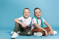 Full length portrait of cute twin brothers sitting. On color background stock image