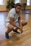 Full length portrait of dancer crouching in studio Stock Images