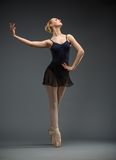 Full-length portrait of dancing ballerina with hand on hips Royalty Free Stock Photo