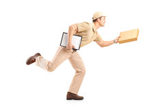 Full length portrait of a delivery boy in a rush delivering a pa. Ckage isolated against white background Royalty Free Stock Photos