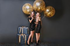 Full-length portrait of dreamy female model with curly hairstyle holding party balloons in her room. Indoor photo of. Pleased girl wears black dress and royalty free stock photography
