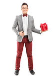 Full length portrait of an elegant man holding a present Royalty Free Stock Image