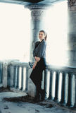 Full length portrait of elegant woman leaning against columns Royalty Free Stock Photo