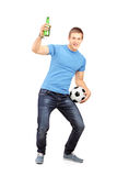 Full length portrait of an euphoric fan holding a beer bottle. And football cheering isolated on white background Stock Photography