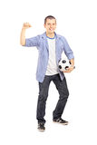 Full length portrait of an euphoric sport fan holding a ball. Full length portrait of an euphoric sport fan holding a soccer ball and cheering isolated on white Royalty Free Stock Image