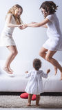 Full length portrait of excited family with arms raised jumping Stock Photography