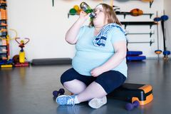 Exhausted Overweight Woman in Gym. Full length portrait of exhausted obese woman sitting on step and drinking water after extreme weightloss workout in fitness Royalty Free Stock Photo