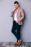 Full length portrait of a fashion man. Standing over gray background royalty free stock photos