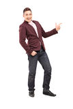 Full length portrait of a fashionable smiling guy pointing with Royalty Free Stock Photos