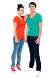 Full length portrait of fashionable young couple. Girl resting her hand on boy's shoulder royalty free stock photo