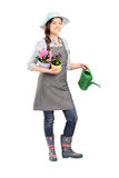 Full length portrait of a female gardener holding flower pots. And watering can isolated on white background Royalty Free Stock Photo