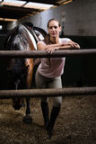 Full length portrait of female jockey. Standing by horse in stable Stock Photos