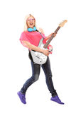 Full length portrait of a female rock star jumping and  playing Royalty Free Stock Photo