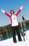 Full-length portrait of female skier with hands up Royalty Free Stock Photography