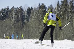 Full length portrait of a female skier standing with one leg raised on a ski slope on a Sunny day against a ski lift. Winter vacat royalty free stock images