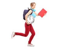 Full length portrait of a female student with clock late for cla Royalty Free Stock Photos