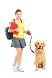 Full length portrait of a female student with dog Royalty Free Stock Images