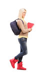 Full length portrait of female student in red boots holding book Royalty Free Stock Image
