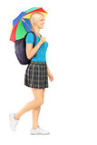 Full length portrait of a female student walking with umbrella Royalty Free Stock Photo