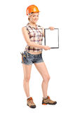 Full length portrait of a female worker showing a blank clipboar Royalty Free Stock Images