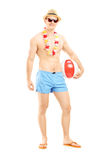 Full length portrait of a fit man in swimming shorts, holding a Stock Photos