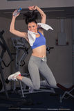 Full length portrait of fit woman jumping in gym Stock Image