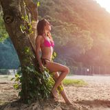 Full-length portrait of fit young woman in pink bra and black panties sitting on tree trunk wearing sunglasses with Royalty Free Stock Photos