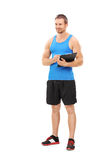 Full length portrait of a fitness coach holding a clipboard Royalty Free Stock Image