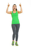 Full length portrait of fitness woman pointing on copy space Stock Photography