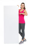 Full length portrait of fitness woman showing blank billboard Stock Image