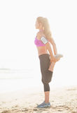 Full length portrait of fitness young woman stretching on beach Royalty Free Stock Photo