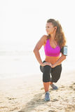 Full length portrait of fitness young woman stretching on beach Royalty Free Stock Photography