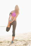 Full length portrait of fitness young woman stretching on beach Stock Image