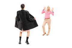 Full length portrait of a flasher scaring a young woman. Isolated on white background Royalty Free Stock Photos