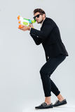 Full length portrait of focused businessman shooting with water gun. Full length portrait of focused businessman in sunglasses and suit shooting with water gun stock images