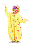Full length portrait of  a funny circus clown gesturing with han Royalty Free Stock Image