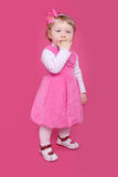 Full length portrait of funny little girl standing over pink bac Stock Photo