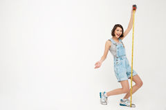 Full length portrait of a funny pretty girl, holding measure tap Stock Photography