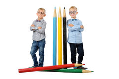 Full length portrait funny young boys in glasses and bowtie posing near huge colorful pencils. Educational concept. Isolated over Stock Image