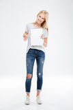 Full length portrait of girl pointing pencil at blank notebook Royalty Free Stock Images