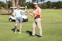 Full length portrait of golfer couple celebrating success. While standing on field Stock Image