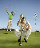 Full length portrait of golfer lining up shot with man jumping in background. Full length portrait of golfer lining up shot with men jumping in background Stock Photo