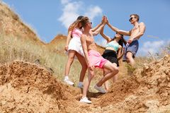 A full-length portrait of a company of teens on a top of a hill gives five each other on a natural blurred background. Royalty Free Stock Photo