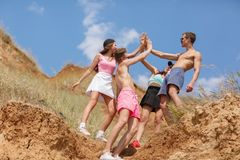 A full-length portrait of a company of teens on a top of a hill gives five each other on a natural blurred background. A full-length portrait of a group of Royalty Free Stock Photo