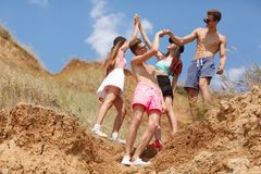 A full-length portrait of a group of teens on a top of a hill gives five each other on a natural blurred background. Stock Photo