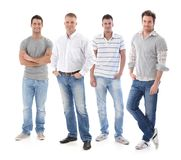 Full-length portrait of group of young men. Wearing jeans, looking at camera, smiling Royalty Free Stock Images