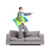 Full length portrait of guy in pajamas sleepwalking on sofa stock photos