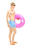 Full length portrait of a guy in shorts holding a swimming ring Royalty Free Stock Photo