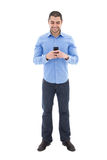 Full length portrait of handsome arabic man in blue shirt. With smartphone isolated on white background Stock Images